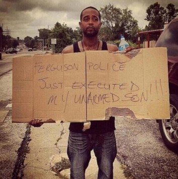 Mike Borwn's stepfather holds a sign accusing police of shooting his unarmed son just hours after the shooting.