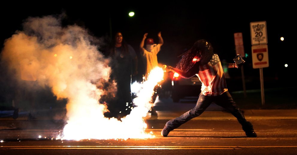 Image #: 31361509 A demonstrator throws back a tear gas container after tactical officers worked to break up a group of bystanders on Chambers Road near West Florissant on Wednesday, Aug. 13, 2014. (Robert Cohen/St. Louis Post-Dispatch/MCT) St. Louis Post-Dispatch/ MCT /LANDOV